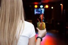Un cocktail arancio freddo con una paglia e una ciliegia blu nelle mani di una ragazza fotografia stock libera da diritti