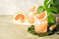 Un cocktail di rinfresco di estate del fondo concreto grigio dei calici di vetro del succo del champagne del pompelmo con le fogl fotografia stock