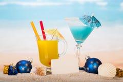 Un cocktail, vetro di succo d'arancia, carta in bianco, palle a di Natale Fotografia Stock
