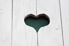 Un coeur découpé sur le mur en bois blanc Image libre de droits