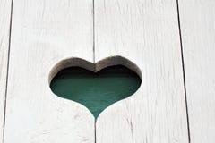 Un coeur découpé sur le mur en bois blanc Images stock