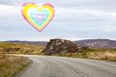 Un coeur d'arc-en-ciel au-dessus d'un paysage montagneux évident de la route photographie stock
