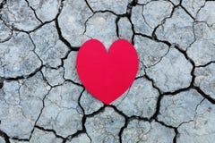 un coeur de papier blanc sur la terre cassée Photographie stock libre de droits