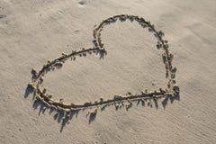 Un coeur dessiné dans le sable Photographie stock libre de droits