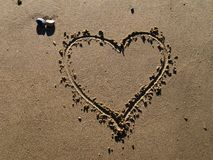 Un coeur dessiné en sable image stock