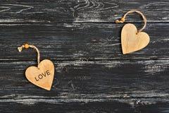 Un coeur en bois avec l'amour de mot sur un vieux fond en bois noir Jour du `s de Valentine Photo libre de droits