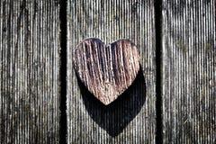 Un coeur en bois de vintage sur les planches en bois grunges. Amour Photo libre de droits