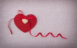Un coeur en bois rouge avec un arc en soie de ribon là-dessus Images libres de droits