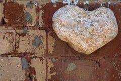Un coeur en pierre blanc, découpé d'une pierre énorme, sur un mur de briques avec des restes de la peinture marron, un symbole de Photographie stock libre de droits
