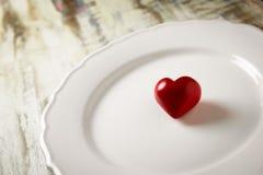Un coeur en pierre rouge dans un plat blanc Image stock