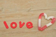 Un coeur fabriqué à partir de des cannes de sucrerie avec l'amour de mot Image libre de droits