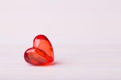 Un coeur facetté par rouge en plastique sur le fond clair Photos libres de droits