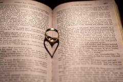 Un coeur fait à partir de l'ombre d'un anneau sur un livre Photographie stock