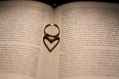 Un coeur fait à partir de l'ombre d'un anneau sur un livre Image stock