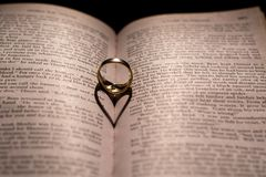 Un coeur fait à partir de l'ombre d'un anneau sur un livre Photos stock