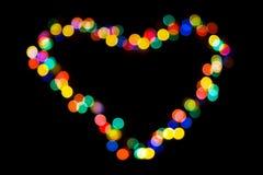 Un coeur fait de lumières colorées sur le noir Photos stock