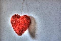 Un coeur rouge ardent accrochant par un fil comme l'amour dans le monde Images libres de droits