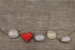 Un coeur rouge avec des pierres sur le fond en bois Carte de voeux FO Photo libre de droits
