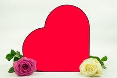 Un coeur rouge avec deux roses du côté photo stock
