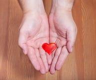 Un coeur rouge dans des mains masculines Image stock