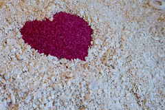 Un coeur rouge dans le sable sur le sable blanc du corail Photo stock
