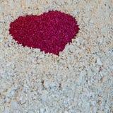 Un coeur rouge dans le sable sur le sable blanc du corail Images stock
