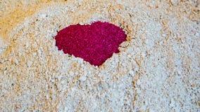 Un coeur rouge dans le sable sur le sable blanc du corail Photo libre de droits