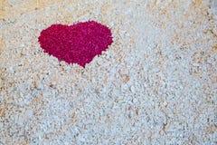 Un coeur rouge dans le sable sur le sable blanc du corail Image stock