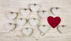 Un coeur rouge dans une collection de beaucoup de coeurs blancs sur un vieux sha Image libre de droits