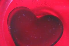 Un coeur rouge en plastique au fond d'un verre de vin rouge Images stock