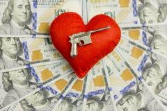 Un coeur rouge et une arme à feu contre le contexte de beaucoup de factures de cent-dollar ont étendu en cercle Amour dangereux d Image stock