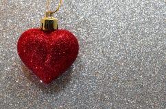 Un coeur rouge solitaire à l'arrière-plan d'argent de scintillement Photographie stock
