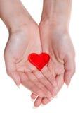 Un coeur rouge sur les paumes femelles d'isolement Images libres de droits