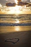 Un coeur sur la plage au coucher du soleil Image stock