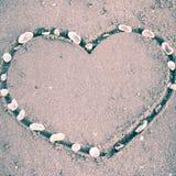 Un coeur sur le sable dans la plage Photo stock