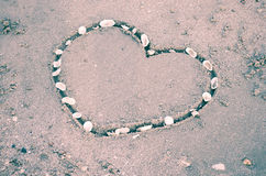 Un coeur sur le sable dans la plage Photos stock