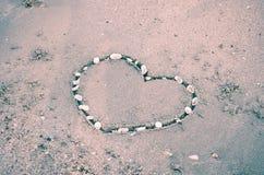 Un coeur sur le sable dans la plage Image stock