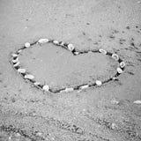 Un coeur sur le sable dans le styl noir et blanc de ton de couleur de plage Images libres de droits