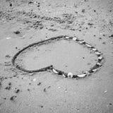 Un coeur sur le sable dans le styl noir et blanc de ton de couleur de plage Photos stock