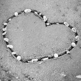 Un coeur sur le sable dans le styl noir et blanc de ton de couleur de plage Images stock