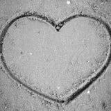 Un coeur sur le sable dans le styl noir et blanc de ton de couleur de plage Image stock