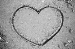 Un coeur sur le sable dans le styl noir et blanc de ton de couleur de plage Photographie stock
