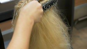 Un coiffeur de styliste se peigne les cheveux à une femme blonde banque de vidéos
