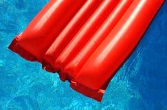 Un colchón inflable rojo en piscina Imágenes de archivo libres de regalías