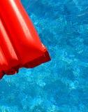Un colchón inflable rojo en piscina Foto de archivo