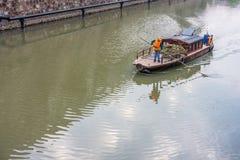 Un colector inútil está recogiendo la basura de un río Fotografía de archivo