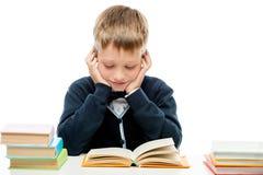 Un colegial con una pila de libros en las lecciones de una lectura de la tabla, un p Fotografía de archivo