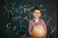 Un colegial que sostiene un globo redondo en las manos de una pizarra pintada con una pizarra imagen de archivo