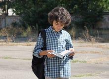 Un colegial rizado con un libro Fotos de archivo