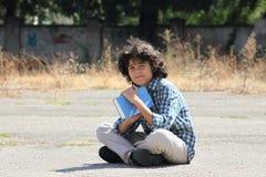 Un colegial rizado con un libro Imagenes de archivo